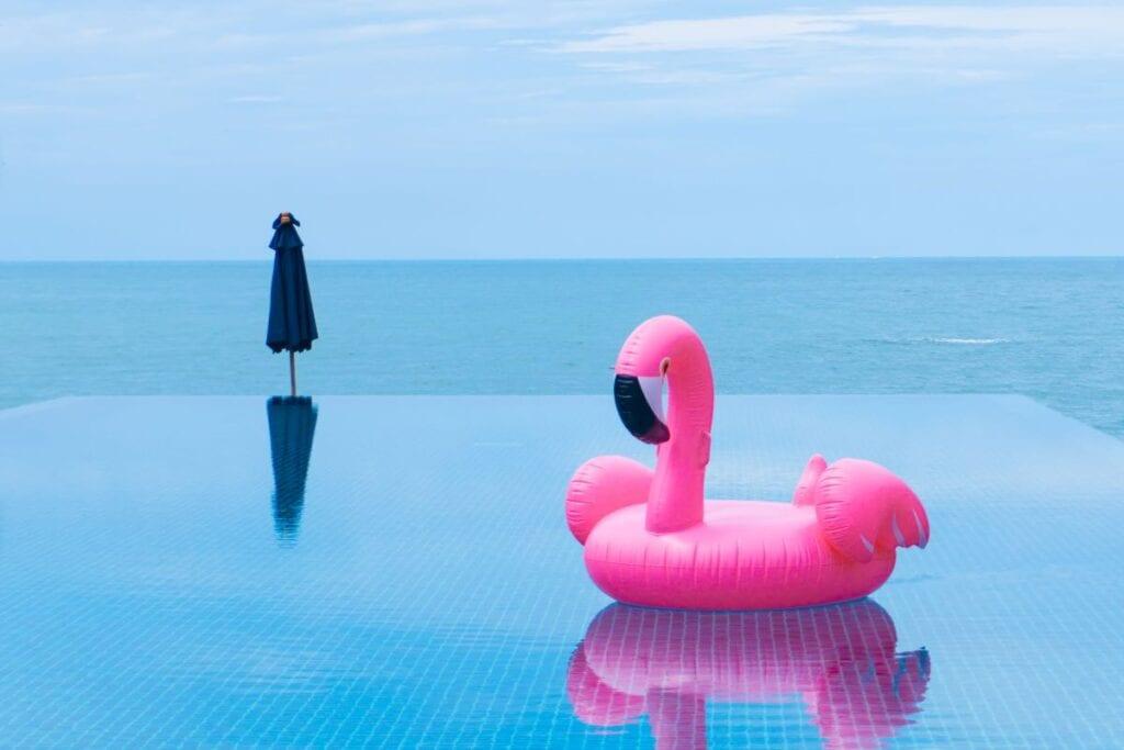 Hot pink flamingo pool float in infinity pool overlooking the sea