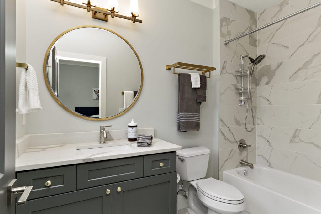 This images shows a modern bathroom with all new white paint and new marble tiles.