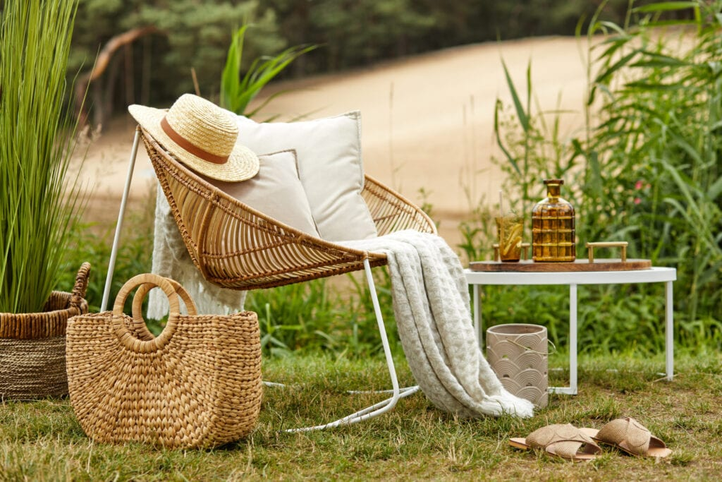 Stylish composition of outdoor garden on the lake with design rattan armchair and elegant accessories. Summer chillout mood.