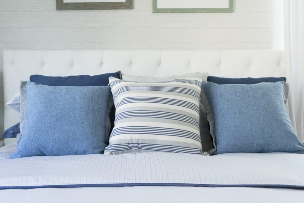 coastal blue cushion on bed in bedroom