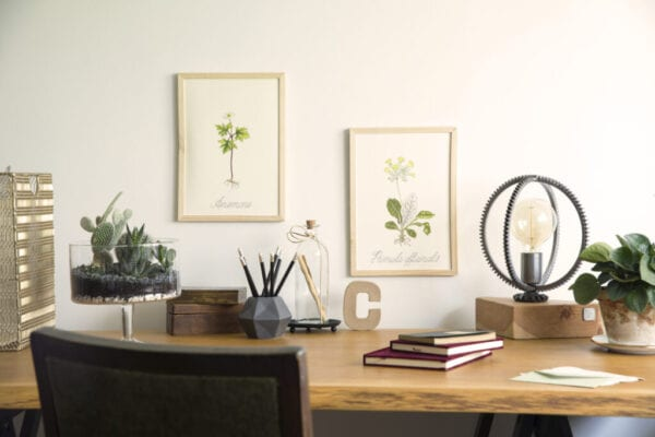 Vintage, creative home office interior with wooden desk, books, laptop, romantic illustrations of plants, lamp and office accessories.