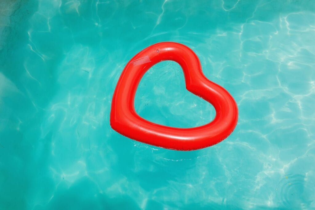 Red heart-shaped pool float in the middle of the pool