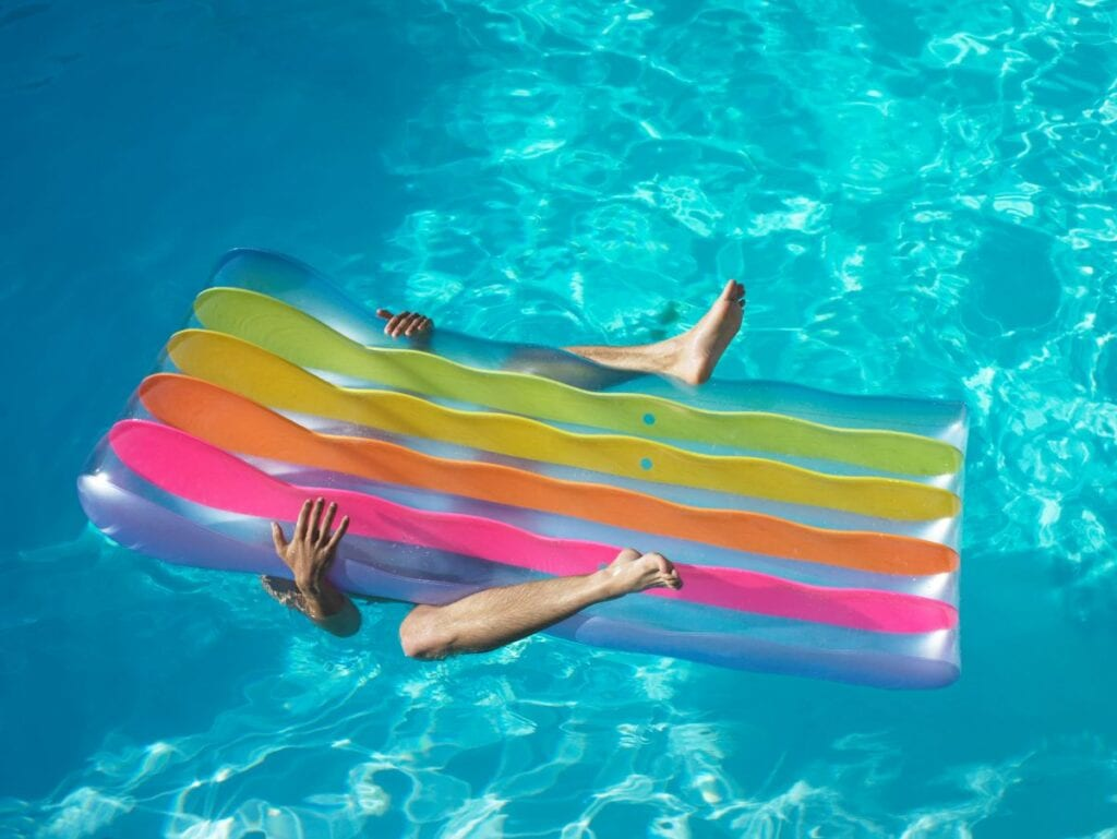 Man laying underneath rainbow pool float