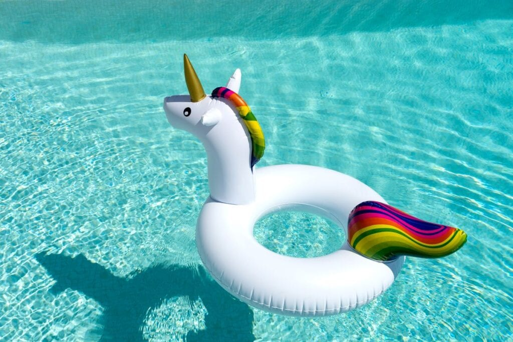 Unicorn shaped pool float in the middle of a swimming pool