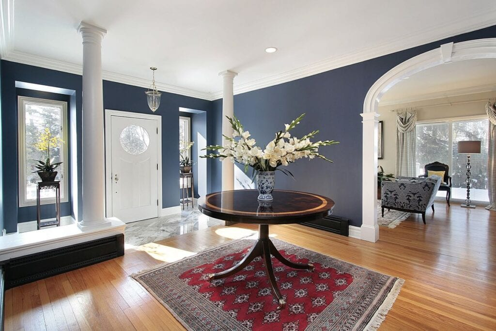 Large foyer with navy blue walls, dark red rug, and white flower centerpiece