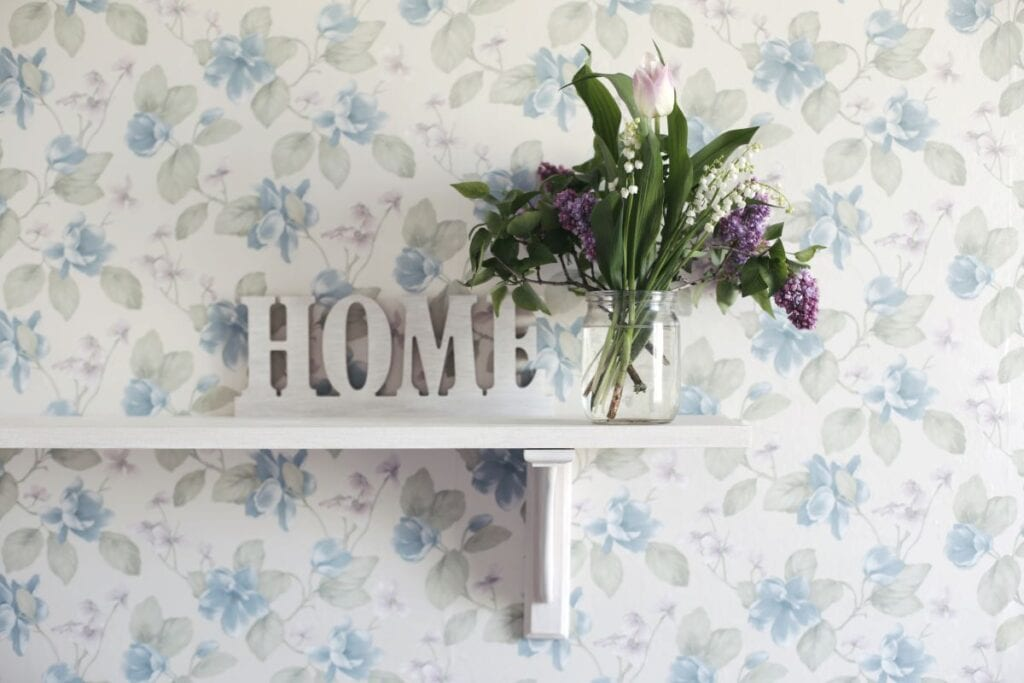 Wall with floral wallpaper and shelf with decor