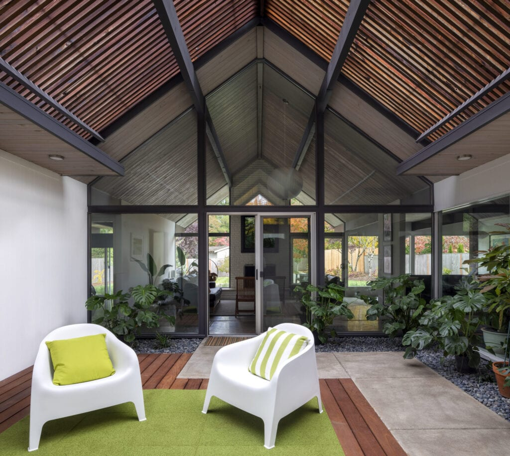 Mid-century modern living space with plants, large windows and a spacious room