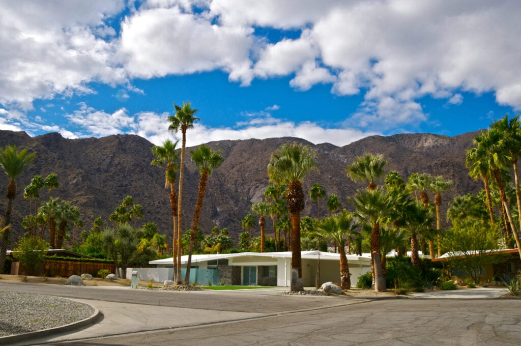 """""""The San Jacinto Mountains are seen in this scenic view in Palm Springs, California. The city is famous for it's many Mid-Century Modern architectural style homes such as the ones in the foreground. California Fan Palm Trees are seen throughout the area, planted when the homes were built. Coachella Valley, Riverside County, Southern California, Western USA."""