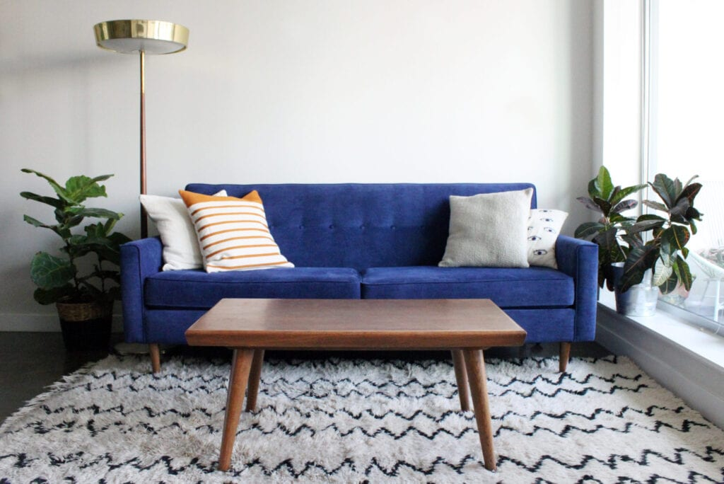 Low angle shot of a royal blue suede mid century modern 4 seater sofa and teak coffee table. Set in a modern apartment living room complete with mid century furnishings, moroccan rug and potted plants.