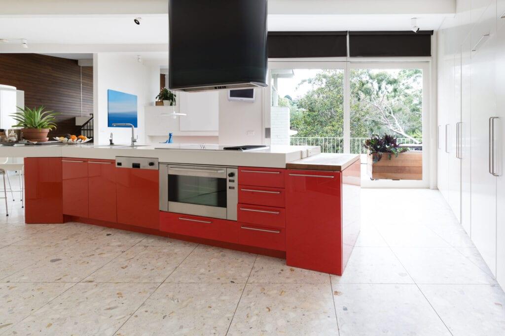Orange red kitchen cabinets in island bench in modern luxury Australian home