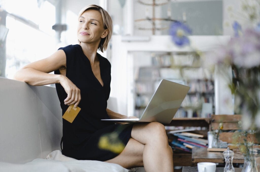 Businesswoman making online payment, sitting in coffee shop, using laptop and credit card