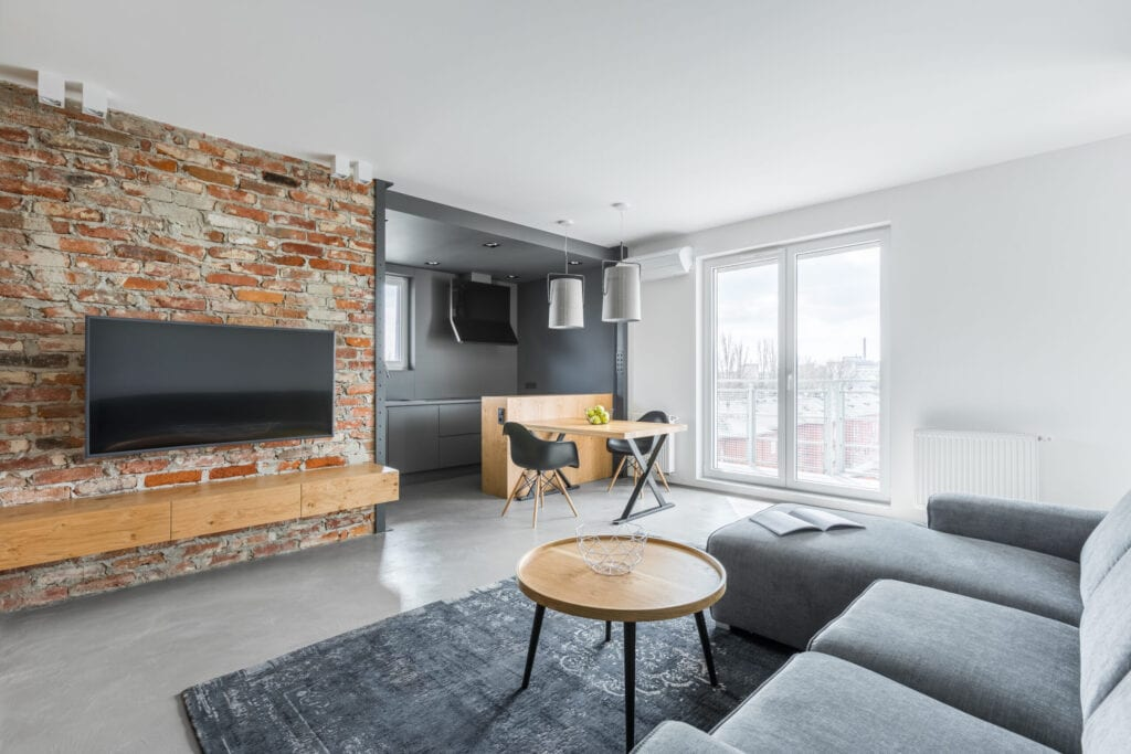Living room with industrial brick wall and gray sofa