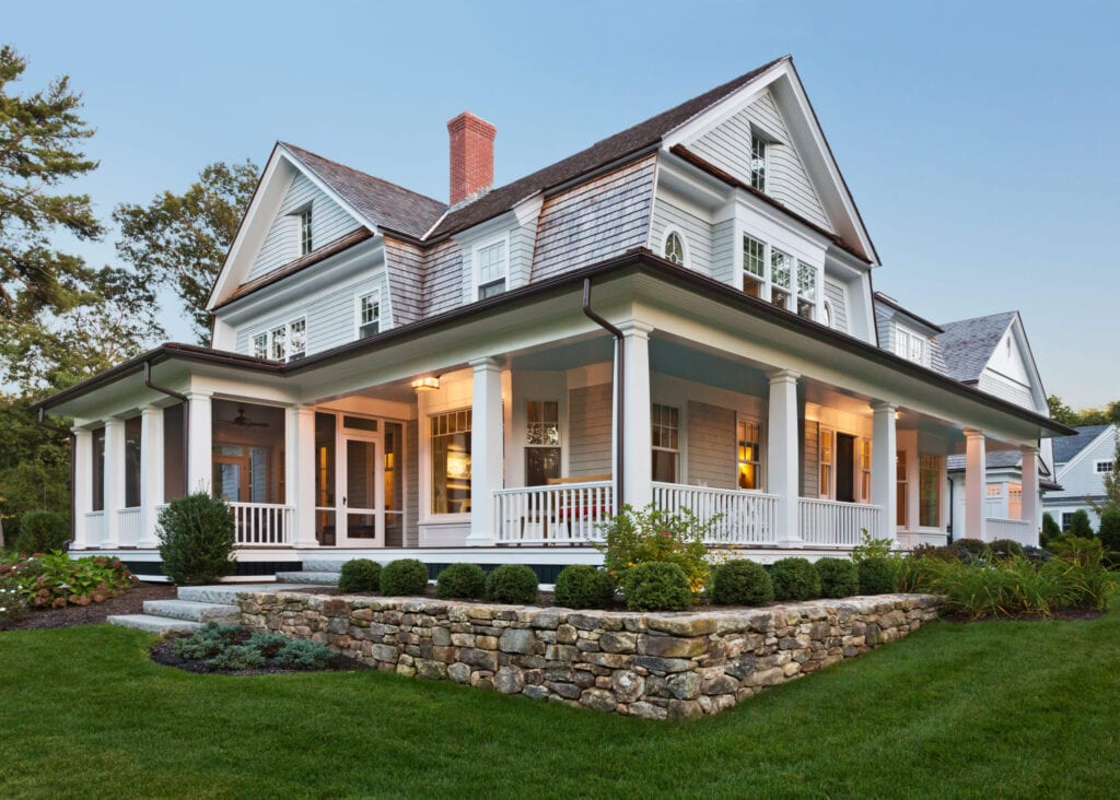 Exterior view of custom built home with exterior lighting and manicured landscaping.