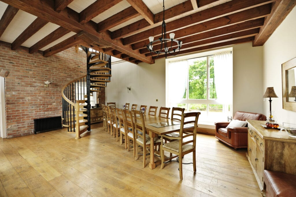 """Luxury dining room with table and 14 chairs, open spiral staircase heading to upper storey, feature brick wall and sofa corner,  in renovated old house. View to garden through window"""""""