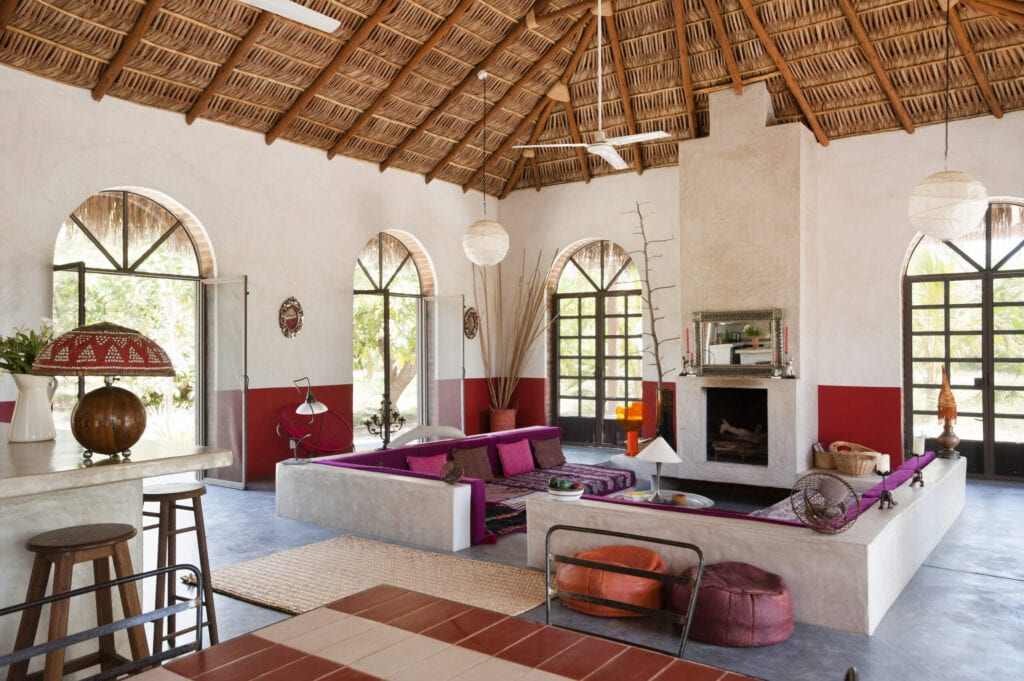 "Open plan sitting room with polished concrete floor, iron framed french windows and a ""Palapa"" roof made from woven palm leaves"