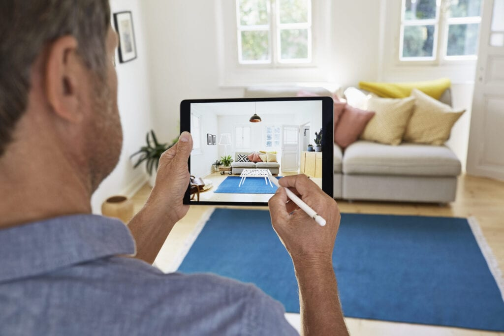 Germany, North-Rhine-Westphalia, Cologne, mature man designing modern living room in a virtual reality with digital pen and tablet