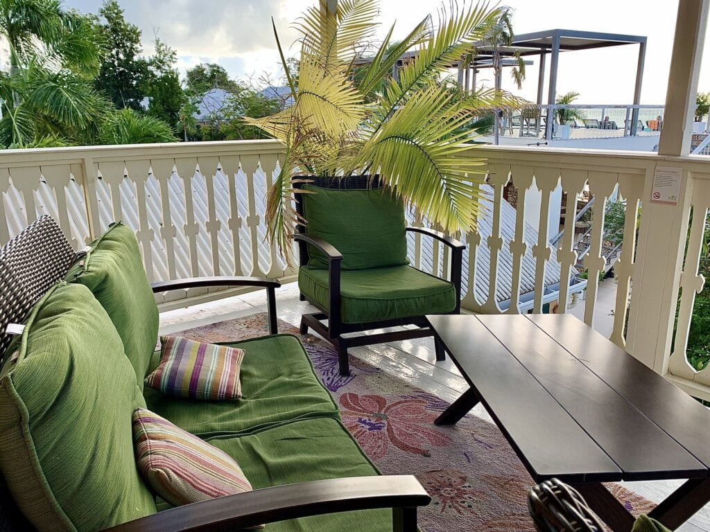balcony furniture with rugs and throw pillows