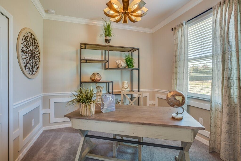Wood desk and large wall clock make this home office functional