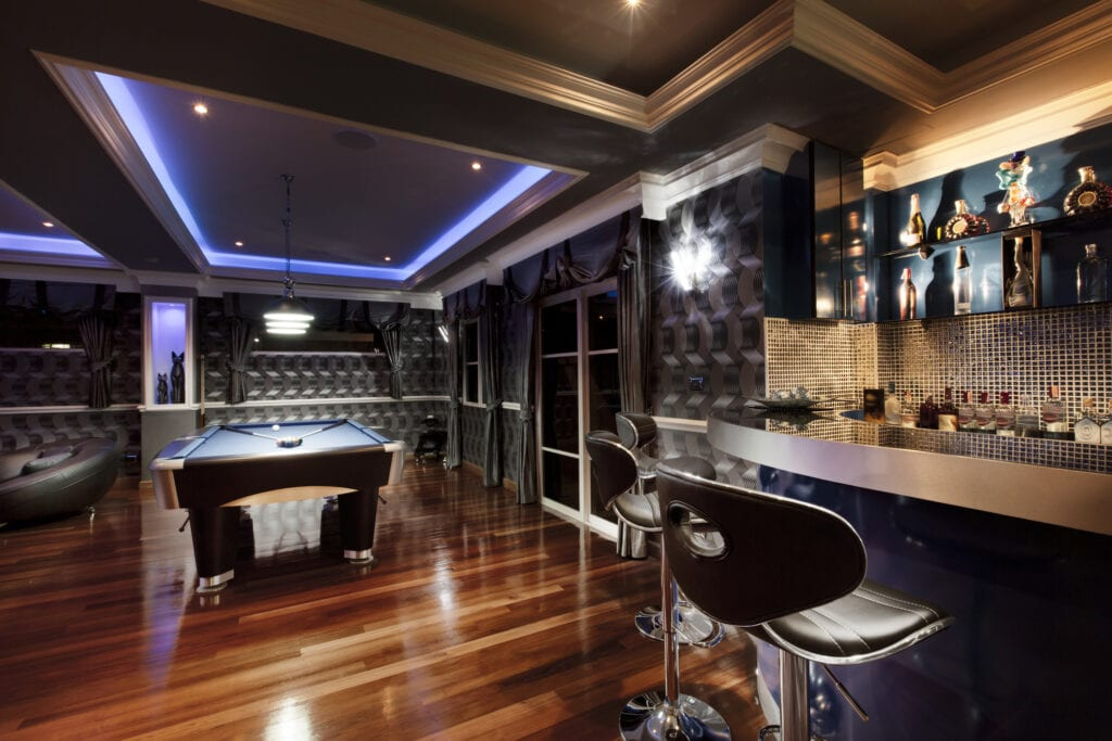 Luxury game room lounge with a bar and pool table