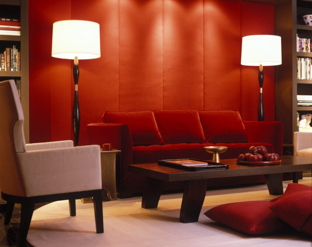Red velvet couch and padded wall in modern living room