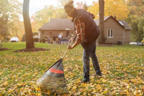man raking leaves in his backyard