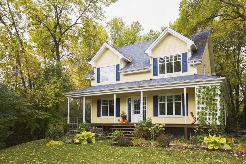 yellow clapboard with blue and white trim cottage style home facade in autumn, Quebec, Canada. This image is property released. CUPR0310