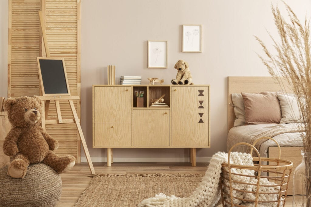 Teddy bear on pouf and small blackboard on easel in stylish kid's bedroom with wooden cabinet and beige bedding on bed