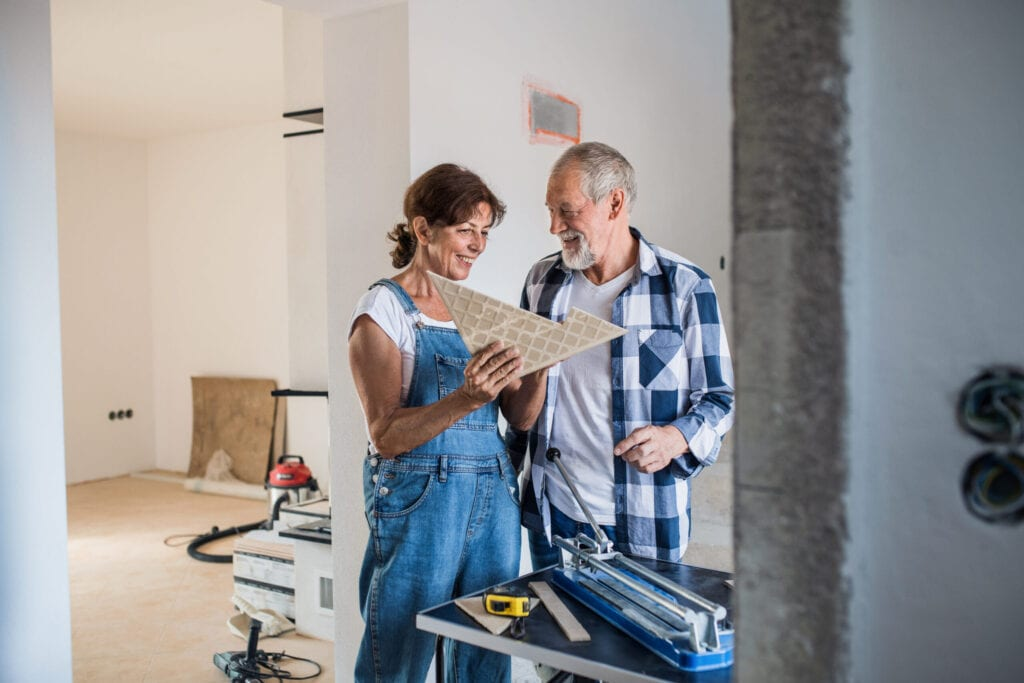 Old man and woman working on interior of new house or flat.