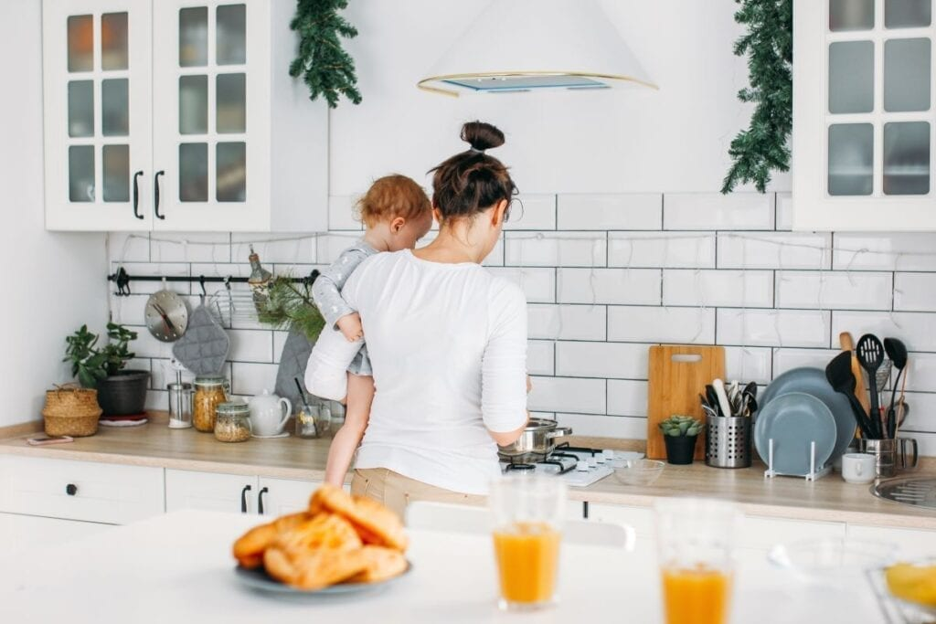 Mom holding baby and cooking breakfast in modern kitchen