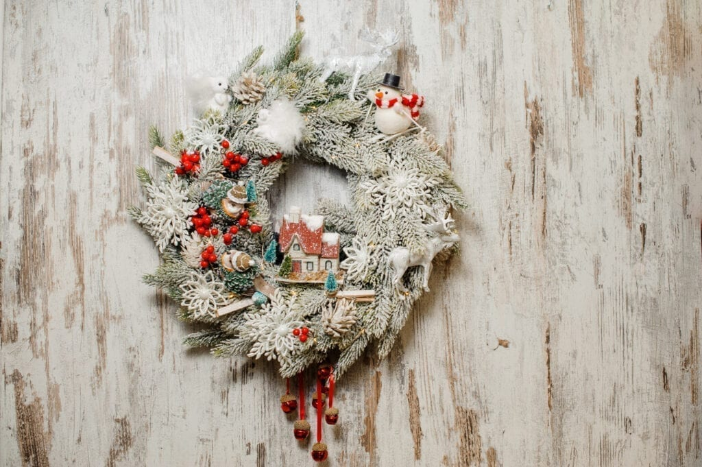 Cute Christmas wreath made of fir tree and stylishly decorated with artificial snow and bright toys