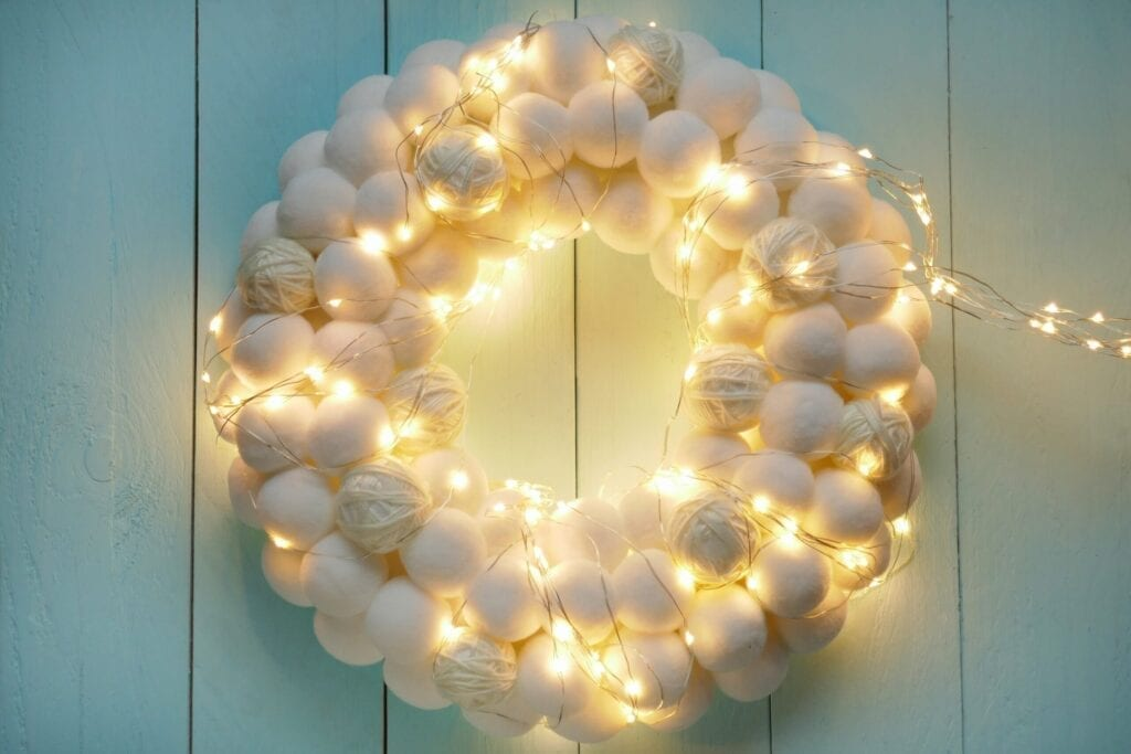 Christmas, New Year's white wreath. round wreath of white soft pompons and shining garland on light blue wooden background.White pompon.Christmas and New Year greeting card. Winter holiday background.
