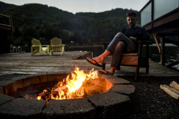 Man sitting on chair by fire pit in Olympic National Park at dusk