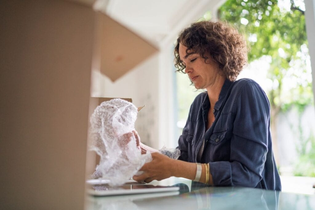 Woman wrapping objects in bubble wrap to prepare for moving