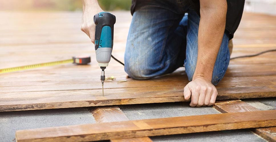 Man with blue drill installing a new deck in his backyard