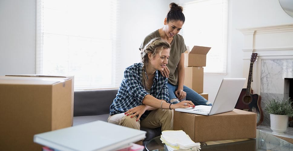 Two women look up moving companies while packing for a move.