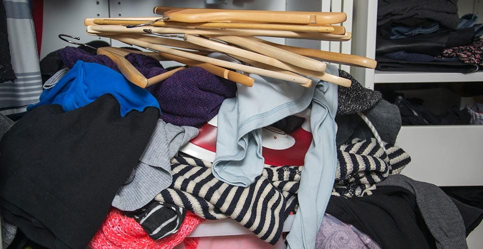 Pile of clothes stacked on a closet floor.