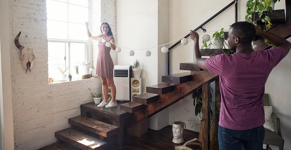 Young millennial couple hangs cafe lights inside of their well-lit minimalistic apartment.