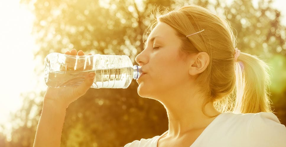 A woman drinks water while moving in the summertime heat.