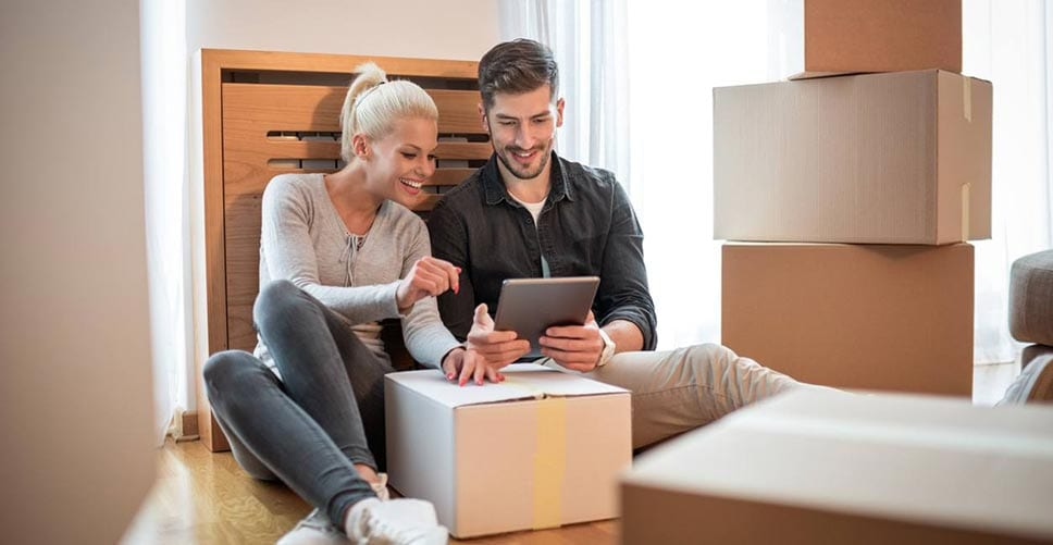 A young couple in the middle of packing sit down to research the cost of hiring professional movers.