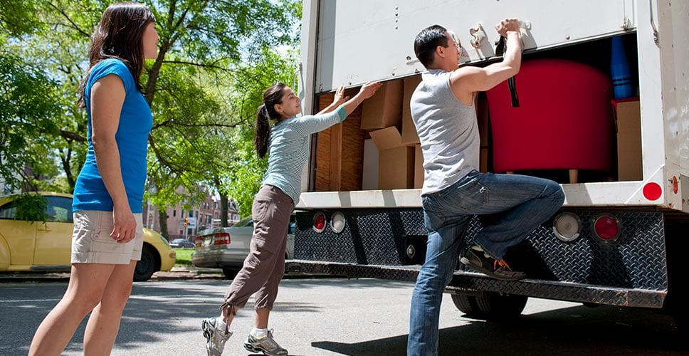 Young people close the back door of a rented moving truck.