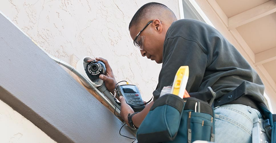 A utility provider checking on outdoor cameras to ensure home safety.