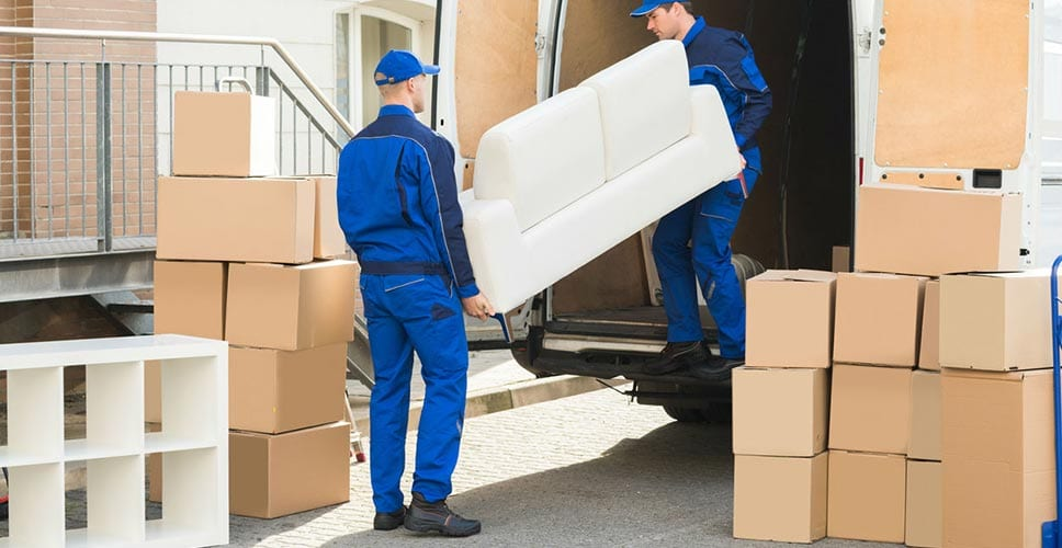 Two movers carefully lift furniture into a moving truck. All the hard work is worth a tip!