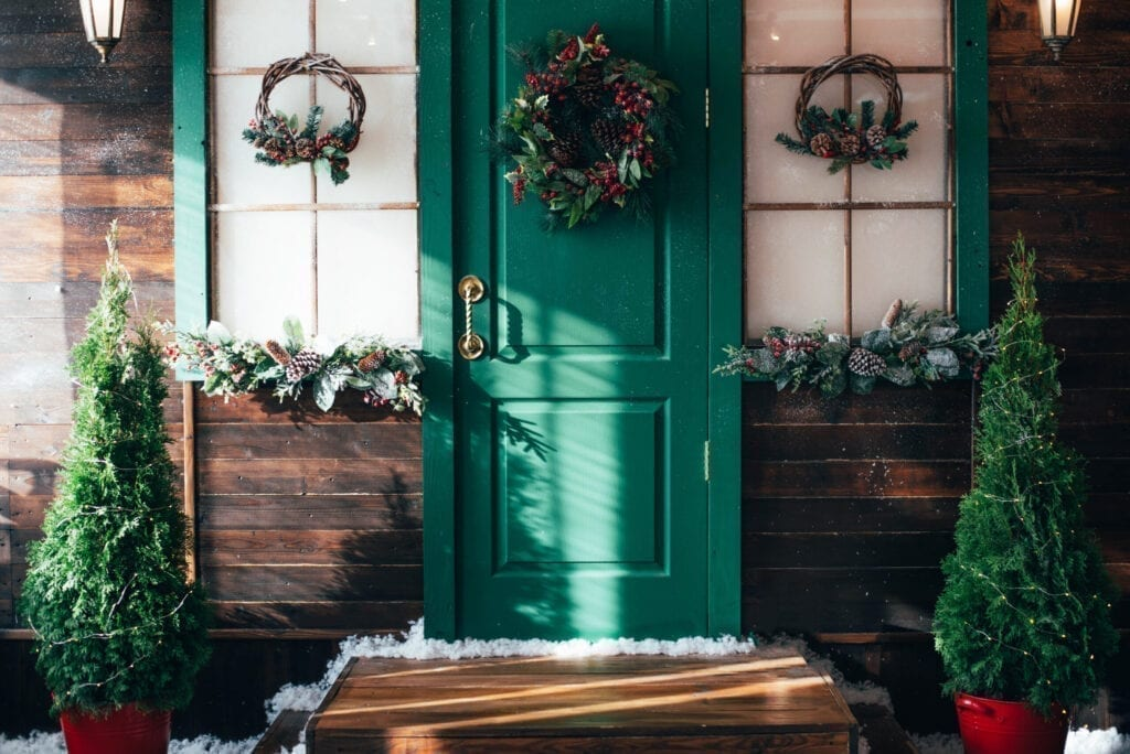 Porch with wooden doors and a threshold with Christmas decor. New year home decoration.