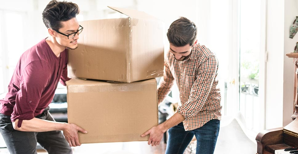 Two professional movers help bring in boxes to a new house.