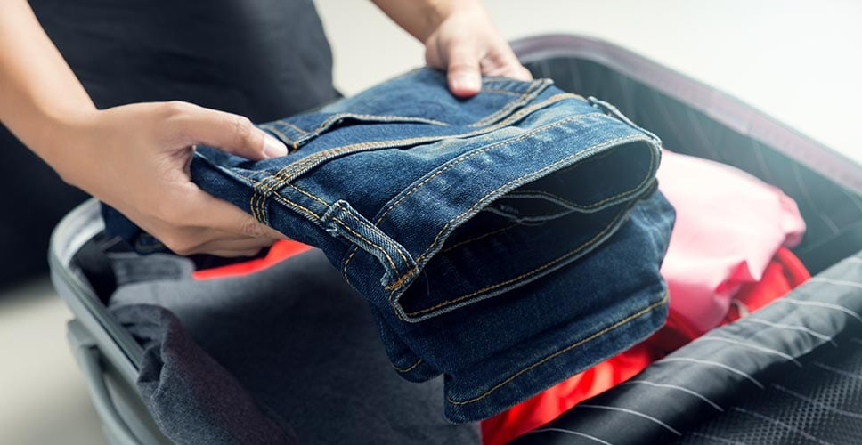 a person packing a pair of jeans into a suitcase