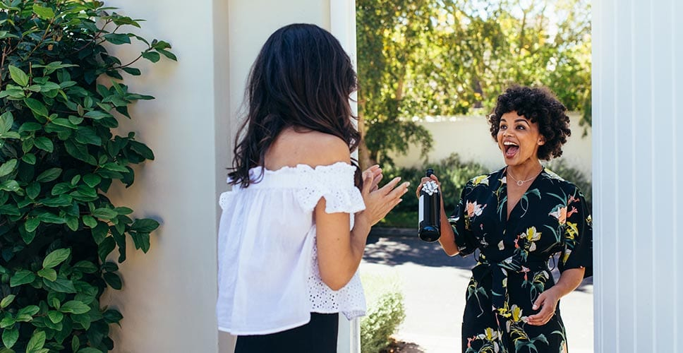 Two young women greet each other at a housewarming party.