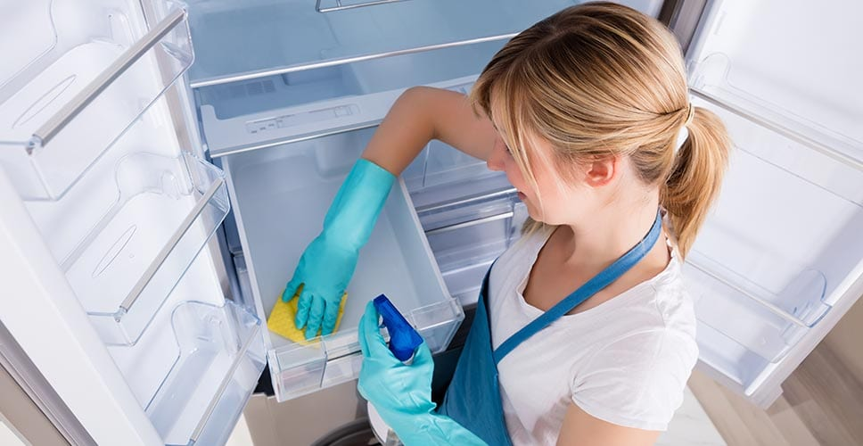 A woman cleans her refrigerator before she moves into her home.