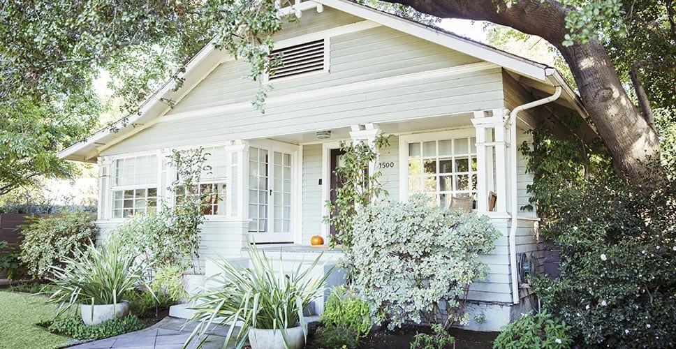 A cute historic home surrounded by lush greenery.