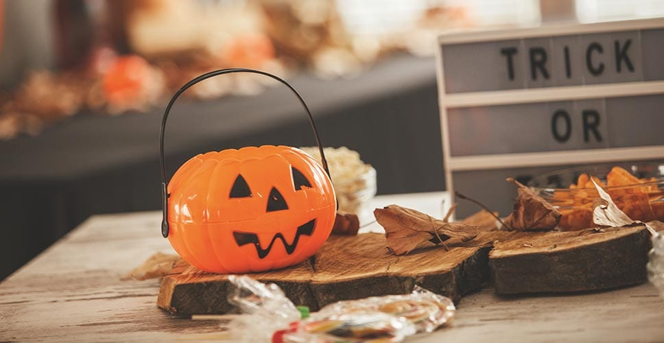 A table decorated for Halloween with a trick or treat sign and a jack-o-lantern basket for candy.