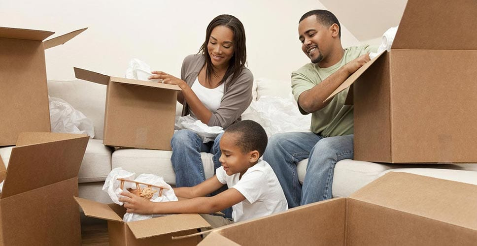 Young family packs boxes with their infant child and prepare for a big move.